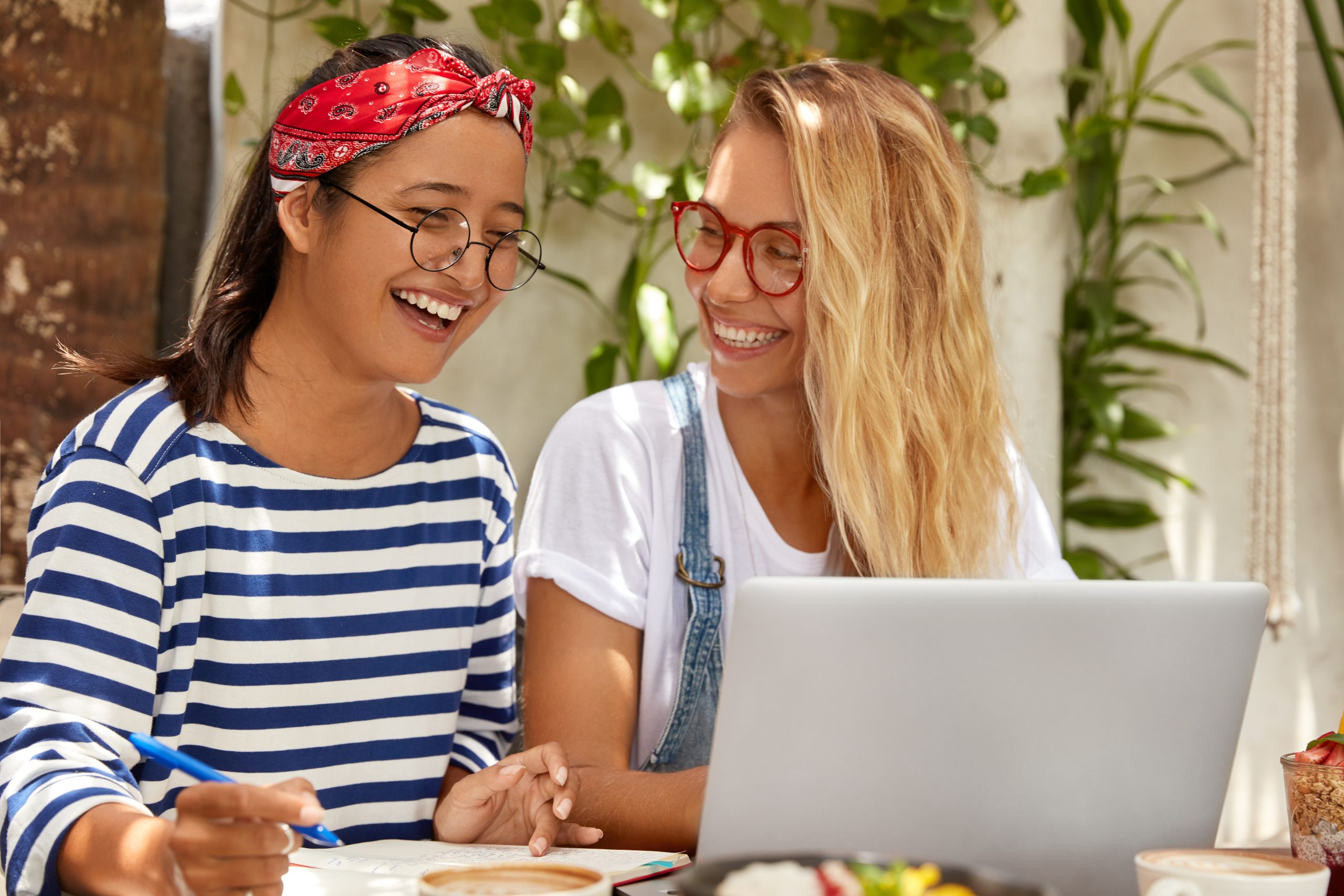 Horizontal view of cheerful mixed race women write article about distant job, learns language by internet, wear round spectacles, drink coffee, have joyful expressions, write notes in notebook