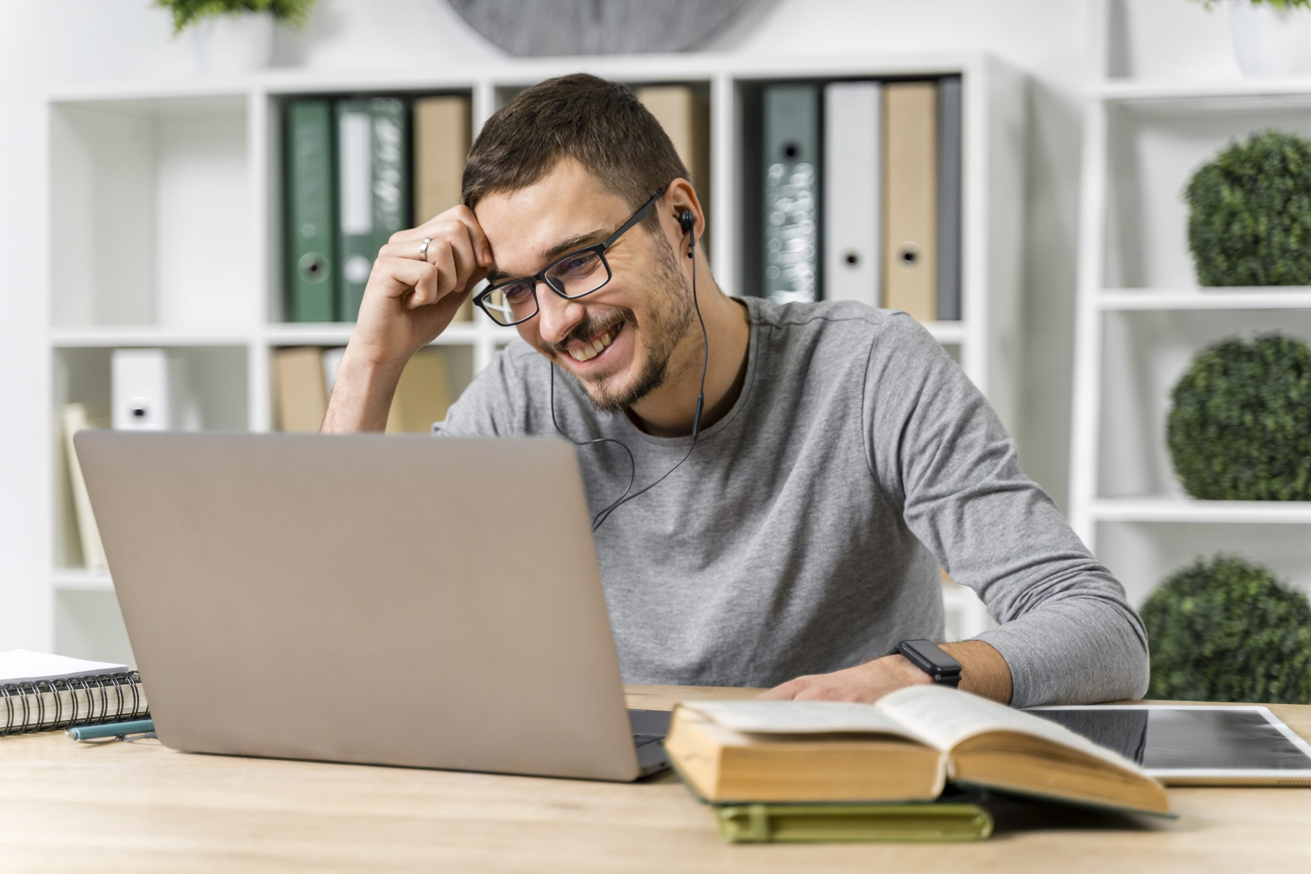 medium-shot-smiley-guy-studying-with-his-laptop